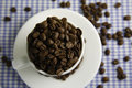 Cup of coffee beans overhead view in and scattered on table Stock Photos