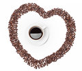 Cup of coffee on beans in shape heart background Royalty Free Stock Photos
