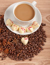 Cup of coffee with beans and white chocolate heart candy  over wooden background Royalty Free Stock Image
