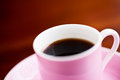Cup of coffee black in a pink and saucer Stock Images