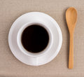 A cup of coffee black and wooden spoon on tablecloth Royalty Free Stock Photo
