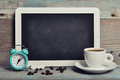 Cup of coffee with blackboard and alarm clock on vintage wooden background Stock Image