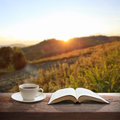 Cup of coffee and a book on a wooden table Stock Photography