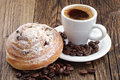 Cup of coffee and bun beans on wooden table Stock Photography