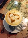 A Cup of coffee cappuccino with a heart of cinnamon on the table in the cafe