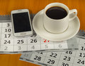 Cup of coffee, cell phone, calendar on wooden table