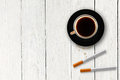 Cup of coffee with cigarettes on the wooden table plank Stock Images