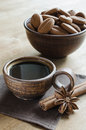 Cup coffee, cinnamon sticks and star anise with cookies on a wooden table. Royalty Free Stock Photo