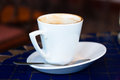 Cup of coffee close up white on dark blue table Royalty Free Stock Image