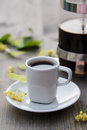 Cup of coffee, coffee pot and linden flower on the table Royalty Free Stock Photo