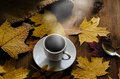 Cup of coffee costs on a wooden table surrounded by autumn leaves Stock Photo