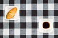 Cup of coffee and croissant on black white checkered tablecloth Royalty Free Stock Image