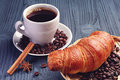 Cup of coffee and croissant on dark blue wooden table Royalty Free Stock Photo