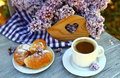 Cup of coffee with croissants and a bouquet of lilacs on the table