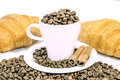 Cup of coffee filed with coffee beans with two croissants and two cinnamon stick Royalty Free Stock Photo