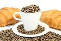 Cup of coffee filed with coffee beans with two croissants on white table Royalty Free Stock Photo