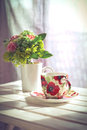 Cup of coffee and flowers on white wooden table retro colors Stock Photos