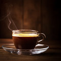 Cup of coffee with fume on the wooden background Stock Images
