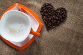 Cup of coffee and heart of coffee beans on linen textile Stock Photo