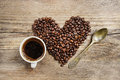 Cup of coffee and heart made of coffee beans Stock Photography