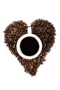 Cup of coffee in heart shaped coffee beans a white filled with the middle Stock Photography