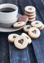 Cup of coffee and heart shaped cut out cookies with chocolate filling Royalty Free Stock Photo