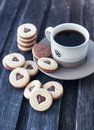 Cup of coffee and heart shaped cut out cookies with chocolate filling Royalty Free Stock Photos