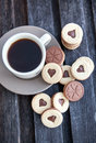 Cup of coffee and heart shaped cut out cookies with chocolate filling Royalty Free Stock Image