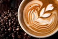 A cup of coffee with latte art some roasted beans background Royalty Free Stock Photography