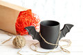 Cup of coffee like a bat in  red paper packaging for Halloween. White background. Toy  and  ball  yarn.  concept. Royalty Free Stock Photo