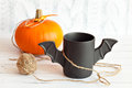 Cup of coffee like a bat in  red paper packaging for Halloween. White background. Toy , pumpkin and  ball  yarn Royalty Free Stock Photo