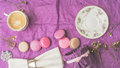 Cup of coffee with macaroons and decoration on the purple paper top view Royalty Free Stock Photo