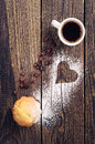 Cup of coffee and muffin on vintage wooden background with heart Stock Photography