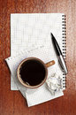 Cup of coffee notebook and pen crumpled paper on table Royalty Free Stock Photography
