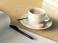 Cup of coffee and notepad with pen Stock Image