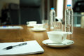 Cup of coffee with pens and paper on wooden table in conference Royalty Free Stock Photo