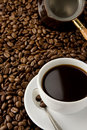 Cup of coffee and pot on beans Royalty Free Stock Images