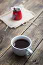 Cup of coffee and pot on wooden background Royalty Free Stock Images