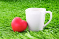 Cup of coffee with red heart on green grass Royalty Free Stock Photo