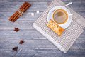 Cup of coffee on saucer with spoon. Vanilla sticks. Star anise and gray napkin Royalty Free Stock Photo
