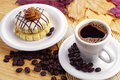 Cup of coffee and small cake round on wooden table Royalty Free Stock Images