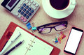 A cup coffee smart phone and office supplies on the table. Royalty Free Stock Photo