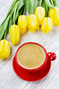 Cup of coffee and spring yellow tulips Royalty Free Stock Photo
