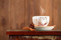 Cup of coffee with steam cinnamon anise on a beautiful rustic background Royalty Free Stock Photography