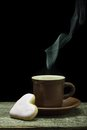 Cup of coffee with steam and heart shape cookies on black background beautiful Stock Photos