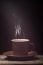 Cup of coffee with steam on wooden board black background grunge Stock Image