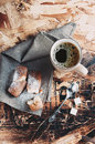 A cup of coffee sugars and metal spoon biscuits sprinkled with sugar on a napkin wooden table Stock Photos