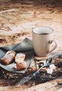 A cup of coffee sugars and metal spoon biscuits sprinkled with sugar on a napkin wooden table Royalty Free Stock Photography