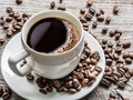 Cup of coffee surrounded by coffee beans. Top view. Royalty Free Stock Photo
