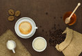 Cup of coffee on the table with beans sugar and honey towel bag milk Royalty Free Stock Image
